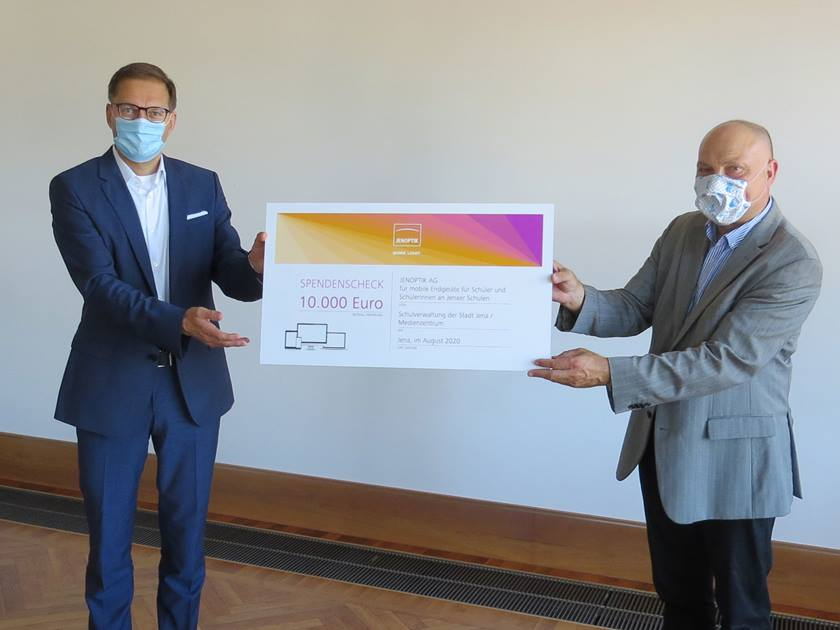 Jenoptik CEO Stefan Traeger hands over a donation cheque for Jena schools